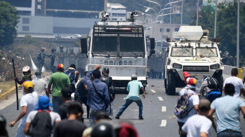 Manifestantes de la oposición se enfrentan a soldados leales al dictador venezolano Nicolás Maduro después de que las tropas se unieran al presidente encargado Juan Guaidó en su campaña para terminar con la usurpación por parte de Maduro, en los alrededores de la base militar de La Carlota en Caracas el 30 de abril de 2019.  (FEDERICO PARRA/AFP/Getty Images)
