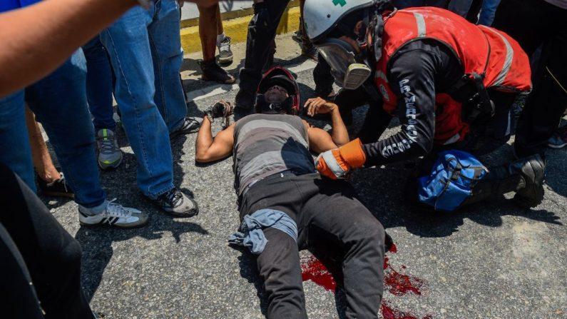 Un manifestante resultó herido cuando las fuerzas de seguridad chavistas utilizaron un vehículo blindado para embestir a los manifestantes durante los enfrentamientos en los alrededores de la base militar de La Carlota en Caracas, el 30 de abril de 2019. (FEDERICO PARRA/AFP/Getty Images)