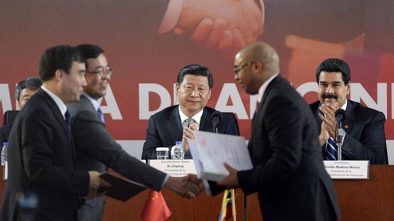 Nicolás Maduro (dcha.) y el mandatario chino Xi Jinping (3º por la dcha.) durante una ceremonia de firma de acuerdos en Caracas el 21 de julio de 2014. (LEO RAMIREZ/AFP/Getty Images)