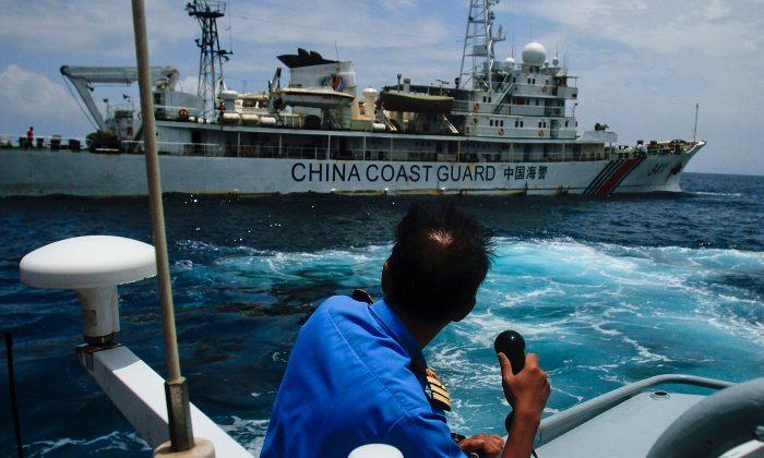 """La milicia marítima china de los """"hombrecitos azules"""" en el Mar de China del Sur. Un miembro de la Armada de Malasia en un intercambio de comunicaciones con un barco de la Guardia Costera China en el Mar de China Meridional, cerca de Kuantan, Malasia, el 15 de marzo de 2014. (Rahman Roslan/Getty Images)"""