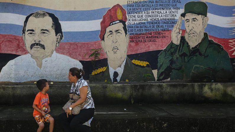Una mujer y un niño se sientan en un banco frente a un mural que representa al presidente de Nicaragua Daniel Ortega (izq.), al difunto presidente de Venezuela Hugo Chávez (izq.) y al dictador de Cuba Fidel Castro en Managua, el 4 de noviembre de 2016. (INTI OCON/AFP/Getty Images)