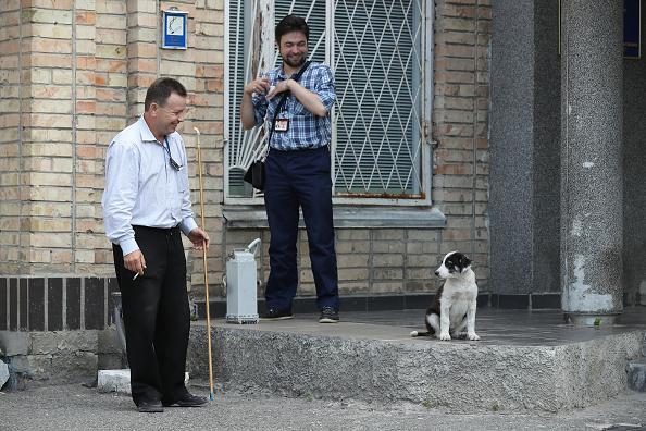CHERNOBYL, UCRANIA - 18 DE AGOSTO: Trabajadores de la administración miran a un perro callejero en la central nuclear de Chernobyl el 18 de agosto de 2017 cerca de Chernobyl, Ucrania.(Crédito: Sean Gallup/Getty Images)