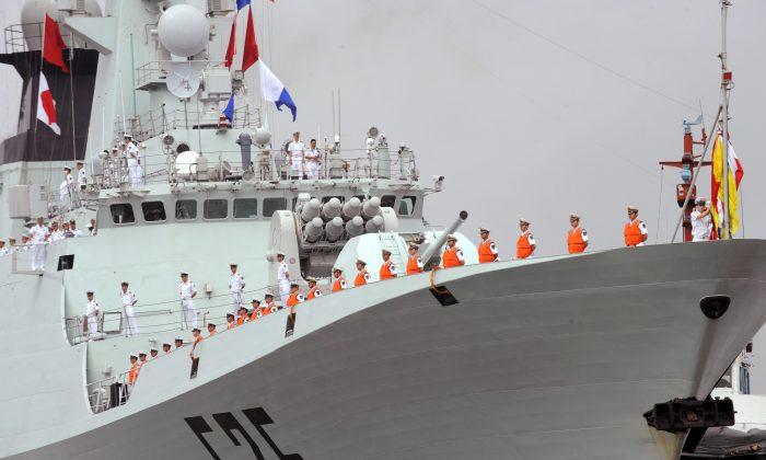 Marineros del Ejército Popular de Liberación (EPL) en la cubierta de un buque de guerra chino en el puerto internacional de Manila el 13 de abril de 2010. (Ted Aljibe/AFP/Getty Images)
