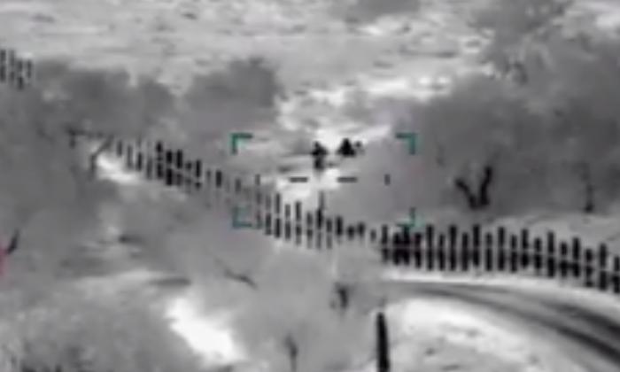 La Aduana y la Patrulla Fronteriza de Estados Unidos publicaron un video que muestra a hombres armados escoltando a una mujer y a su hijo a través de la frontera estadounidense el 20 de abril de 2019. (CBP)