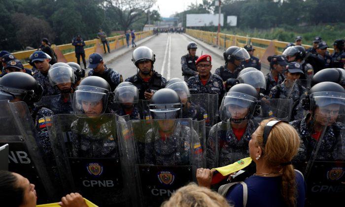 Migrantes piden cruzar la frontera entre Colombia y Venezuela en el Puente Simón Bolivar mientras las fuerzas de seguridad vigilan la línea fronteriza bloqueando el camino en las afueras de Cucuta, Colombia, el 23 de febrero de 2019. (Edgard Garrido/Reuters)