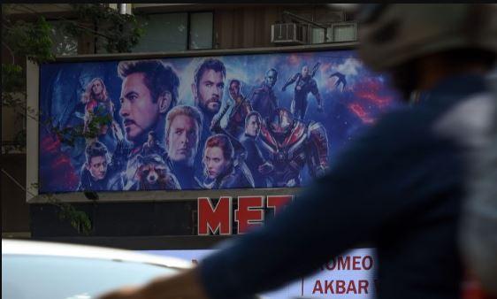 Los vehículos pasan por un cine que muestra un póster de la última película Avengers en Mumbai, India, el día de la premier el 25 de abril de 2019. (Indranil Mukherjee/AFP/Getty Images)
