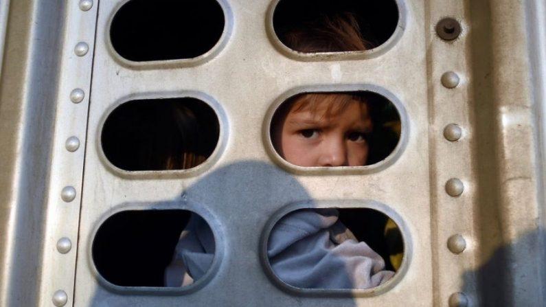Una niña que participa en una caravana de migrantes mira desde el remolque de un camión a lo largo de la carretera Irapuato-Guadalajara en el estado mexicano de Guanajuato, el 12 de noviembre de 2018. (Alfredo Estrella/AFP/Getty Images)