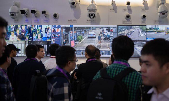 Los visitantes observan cámaras de seguridad de Inteligencia artificial que utilizan tecnología de reconocimiento facial en la 14ª Exposición Internacional de Seguridad Pública de China en el Centro Internacional de Exposiciones de China en Beijing, el 24 de octubre de 2018. (Nicolas Asfouri/AFP/Getty Images)