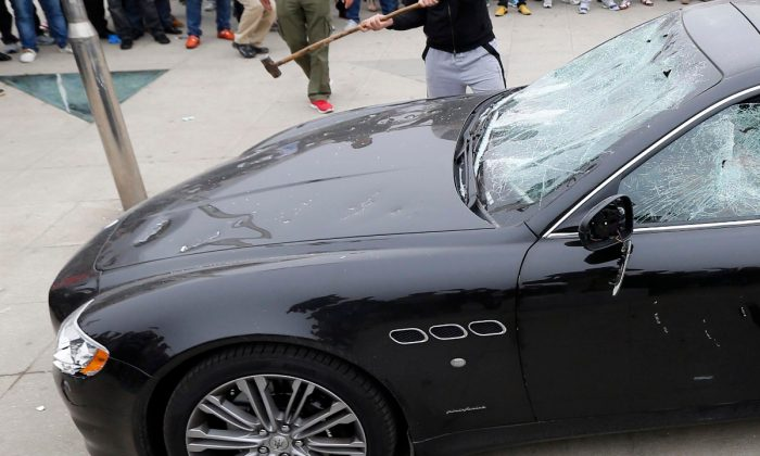 El Maserati de un rico empresario siendo atacado con unmartillo. (STR/AFP/Getty Images)