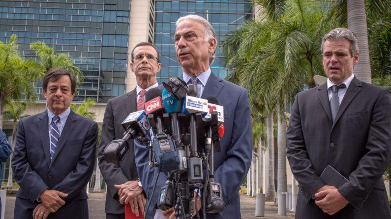 El abogado Roberto Martínez (delante), habla junto a su colega Rodney S. Margol (i atrás), y los demandantes Javier García Bengoechea (c atrás), que dice ser el legítimo propietario del puerto de Santiago de Cuba, y Mickael Behn (d), cuya familia originaria de Kentucky poseía la compañía Havana Docks Corporation en el puerto habanero, durante una conferencia de prensa este 2 de mayo, en el exterior de un tribunal federal en Miami, Florida (EE.UU.). EFE