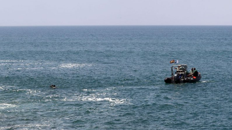 Dos submarinistas y una lancha de la Guardia Civil (i) durante la búsqueda de los inmigrantes desaparecidos en el mar tras desembarcar de una patera en el sur de Gran Canaria. EFE