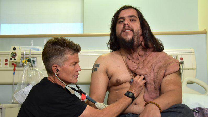 """La doctora especializada en anestesiología, Kim Jiménez, revisa al paraguayo Enrique Galván (d), que sufre la llamada enfermedad del """"hombre elefante"""", la cual le provoca un crecimiento excesivo de la piel en parte de su rostro y cuello, el 30 de mayo, en las dependencias del hospital universitario """"Health Douglas"""" del Centro Médico de la Universidad de California en Irvine (UC Irvine), California (EE.UU.). EFE"""