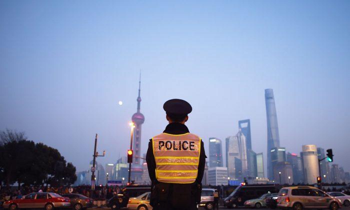 Un oficial de policía hace guardia en el lugar de la estampida de Nochevieja en Shanghai, el 3 de enero de 2015. Las autoridades de Shanghai han endurecido la censura sobre el incidente bloqueando las críticas en línea, convocando a los usuarios de Internet y suprimiendo a la prensa. (Wang Zhao/AFP/Getty Images)