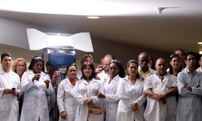 Médicos cubanos participam da sanção da lei que estabelece o Programa Mais Médicos em Brasília, Brasil, em 22 de outubro de 2013 (EVARISTO SA / AFP / Getty Images)