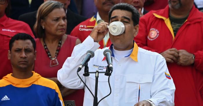 Nicolás Maduro bebe de una taza durante un mitin frente al Palacio Presidencial de Miraflores en Caracas el 20 de mayo de 2019. Foto de MARVIN RECINOS/AFP/Getty Images.