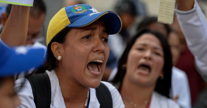"""Trabajadores de la salud protestan durante una protesta por la falta de medicamentos, suministros médicos y malas condiciones en los hospitales, frente al Hospital Infantil """"Dr. JM de los Ríos"""" de Caracas el 16 de agosto de 2018. Foto de FEDERICO PARRA/AFP/Getty Images."""