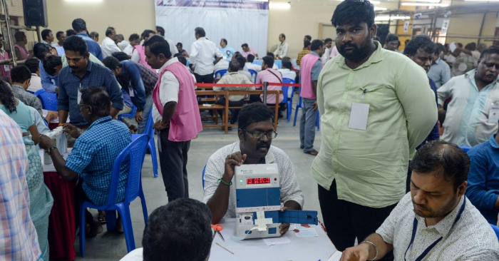Funcionarios electorales indios comprueban una máquina electrónica de votación (EVM) el día de los resultados de las elecciones generales de la India en un centro de recuento de votos en Chennai el 23 de mayo de 2019. Foto de ARUN SANKAR/AFP/Getty Images.