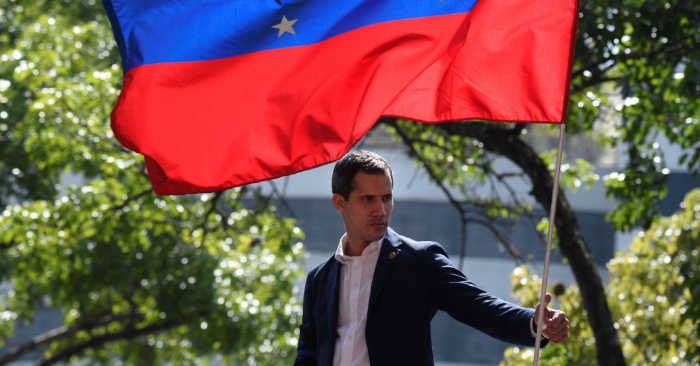 El presidente encargado de Venezuela, Juan Guaidó, es fotografiado con una bandera nacional durante una manifestación después de que miembros de la Guardia Nacional Bolivariana se le unieran a su campaña para poner fin a la usurpación de Nicolás Maduro, en Caracas el 30 de abril de 2019. Foto de FEDERICO PARRA/AFP/Getty Images.