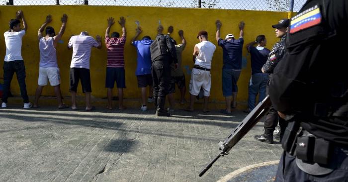 Miembros de las Fuerzas Especiales de Acción de Venezuela (FAES) y un grupo de hombres durante una operación de seguridad en el barrio de los 70, municipio de El Valle, en Caracas, el 1 de abril de 2019. Foto debe ser YURI CORTEZ/AFP/Getty Images.