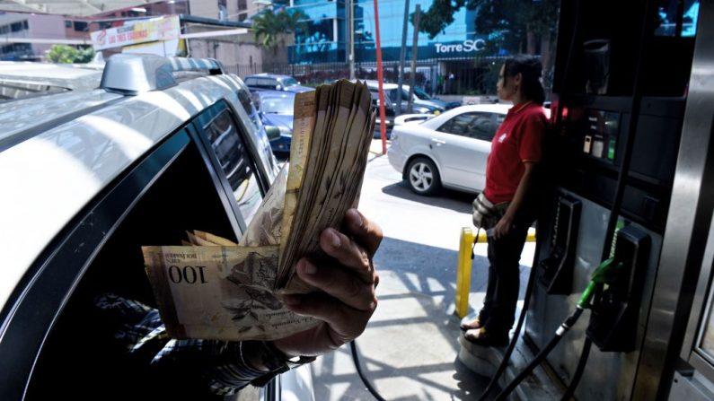 """Un cliente muestra los billetes de Bolívar mientras se encuentra en una estación de servicio en Caracas, donde la gente hace cola para comprar gasolina el 17 de agosto de 2018. El presidente Nicolás Maduro anunció el 13 de agosto de 2018 que el combustible subsidiado de Venezuela estará disponible solo a quienes registren sus vehículos con el """"carnet de la patria"""" que se da a quienes se adhieren a la politica dictatorial del régimen. (FEDERICO PARRA / AFP / Getty Images)"""