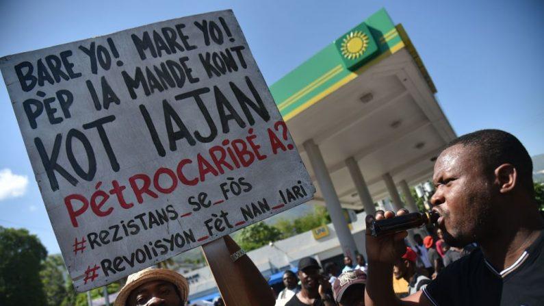 Manifestantes cantan y sostienen afiches durante una manifestación exigiendo que los políticos rindan cuentas por el despilfarro de miles de millones de dólares en ingresos del programa petrolero de Venezuela con descuento PetroCaribe, frente a las oficinas del Tribunal Superior de Cuentas y Litigios Administrativos, en Puerto Príncipe, el 24 de agosto de 2018. (HECTOR RETAMAL/AFP/Getty Images)