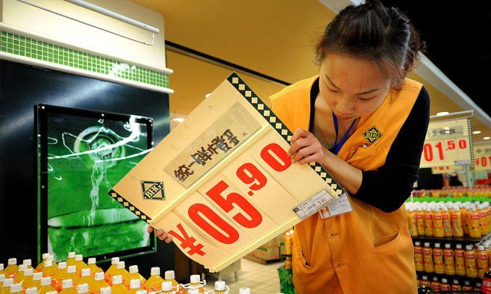 Una empleada china cambia un cartel de precios de alimentos en un supermercado de Hefei, en la provincia de Anhui, en el este de China, el 17 de noviembre de 2010. (STR/AFP/Getty Images)