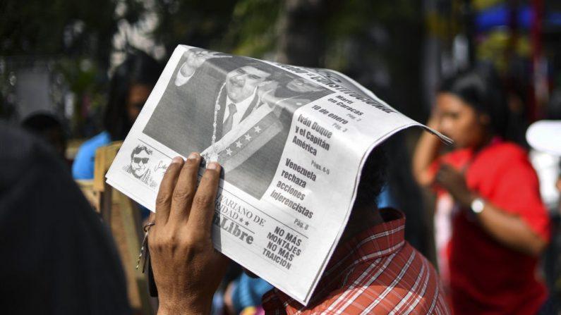 Un hombre se protege del sol con un periódico oficialista que presenta al dictador venezolano Nicolás Maduro en su portada, en la plaza Bolívar de Caracas, el 6 de febrero de 2019. (YURI CORTEZ/AFP/Getty Images)
