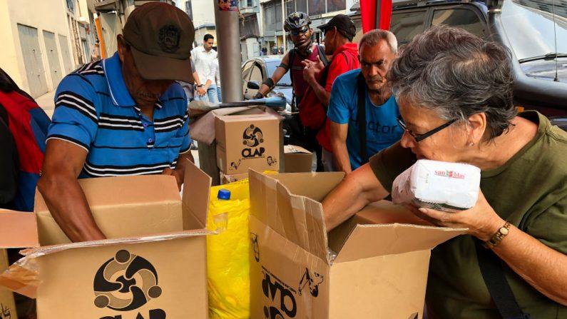 """Vecinos del barrio Unión de Petare abren cajas del programa de alimentos CLAP entregado por """"Colectivo Resistencia y Rebelión de Caracas"""" el 4 de abril de 2019 en Caracas, Venezuela.  (Eva Marie Uzcategui/Getty Images)"""
