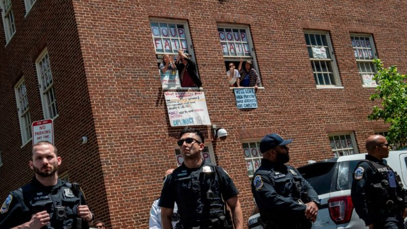Activistas pro-dictadura en Venezuela que ocupaban la embajada venezolana en Washington saludan desde una ventana el 15 de mayo de 2019. (ERIC BARADAT/AFP/Getty Images)