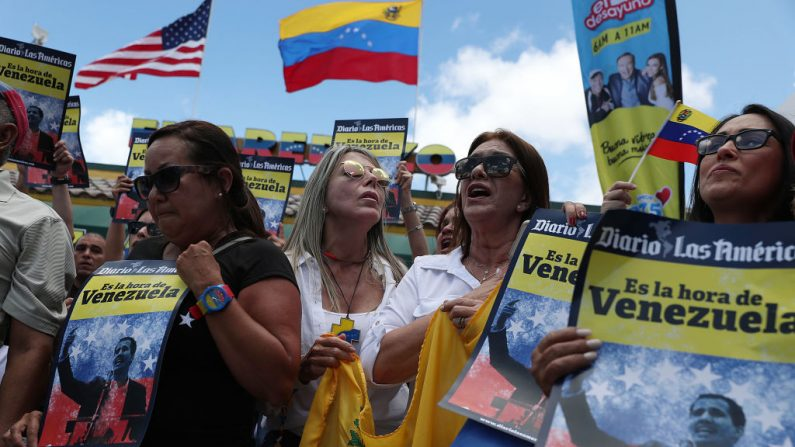 La gente muestra su apoyo al presidente interino de Venezuela, Juan Guaidó, durante un mitin en las afueras del restaurante venezolano El Original El Arepazo, mientras se desarrollan los eventos en el país el 30 de abril de 2019 en Doral, Florida. (Joe Raedle/Getty Images)