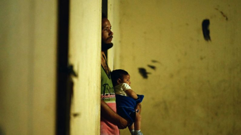 El venezolano Eymir Aponte sostiene a uno de sus hijos en el refugio Jehova Gire, un edificio a medio hacer del poder judicial en el barrio de Petare, Caracas, el 19 de mayo de 2019. Símbolo de la ocupación ilegal desde la época del difunto líder socialista Hugo Chávez (1999-2013), el esqueleto de hormigón es el hogar de indigentes, víctimas de desastres y otros que cayeron en desgracia con la peor crisis económica en la historia reciente del país productor de petróleo. (MARVIN RECINOS/AFP/Getty Images)