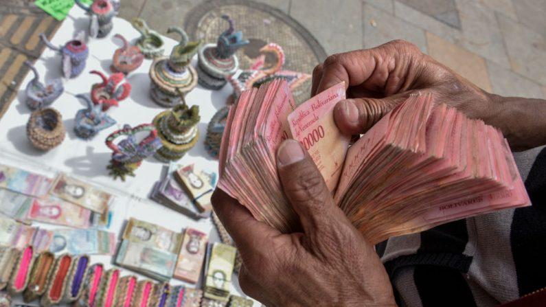 El diseñador colombiano Luis Orlando Ortega cuenta los billetes venezolanos devaluados y fuera de circulación Bolivares Fuertes en la avenida principal del centro histórico de Bogotá, Colombia, el 18 de mayo de 2019. El Sr. Ortega, de 60 años, vivió 43 años en Venezuela, regresó a Colombia hace 2 años, escapando de la crisis económica y social en Venezuela y ahora se gana la vida vendiendo artesanías hechas con los devaluados bolívares venezolanos. (Guillermo Legaria/Getty Images)