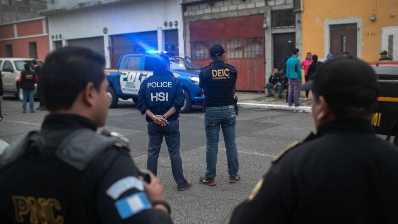 Agentes de Investigaciones de Seguridad Nacional de Estados Unidos (HSI) y la policía guatemalteca se encuentran en el lugar de una redada en la madrugada donde traficantes de personas fueron detenidos el 29 de mayo de 2019 en la Ciudad de Guatemala. (John Moore/Getty Images)