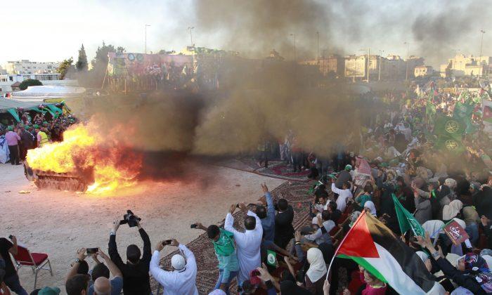 Simpatizantes jordanos de los Hermanos Musulmanes incendian una maqueta de un tanque israelí durante una manifestación para celebrar la 'victoria de Gaza' en la guerra contra Israel, en la capital Amman el 8 de agosto de 2014. (KHALIL MAZRAAWI/AFP/Getty Images)