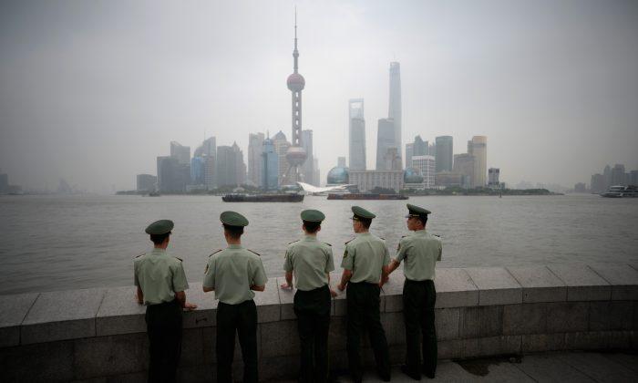 Policías paramilitares parados enfrente del distrito financiero de Lujiazui en Pudong, en el smog de Shanghai. (Johannes Eisele/AFP/Getty Images)