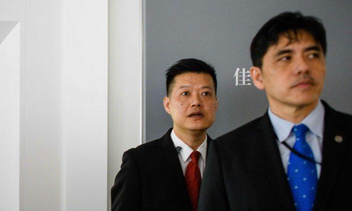 """Esta foto, tomada el 13 de octubre de 2017, muestra a un hombre (Der. de corbata azul) identificado por un medio de comunicación local de Hong Kong como el exagente de la CIA, Jerry Chun Shing Lee, frente a un miembro de la seguridad en la inauguración del cuadro de Leonardo da Vinci """"Salvator Mundi"""" en la sala de exposiciones de Christie's en Hong Kong. (Anthony Wallace/AFP/Getty Images)"""