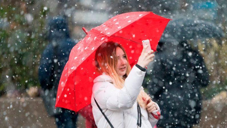 Cruzar la calle distraido mirando el celular podrá significar una multa en Nueva York. . Una mujer toma fotos con su teléfono celular mientras cae una fuerte nevada el 7 de marzo de 2018 en Union Square en Nueva York (DON EMMERT / AFP / Getty Images)