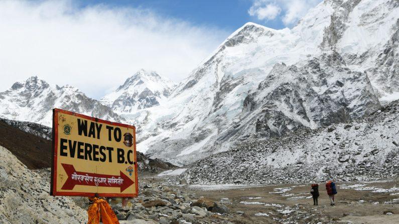 Un letreto apunta hacia el campamento base del Everest, mientras que dos excursionistas caminan en la región del Everest en el distrito de Solukhumbu, unos 140 kilómetros al noreste de la capital de Nepal, Katmandú el 26 de abril de 2018. (Crédito: PRAKASH MATHEMA/AFP/Getty Images)