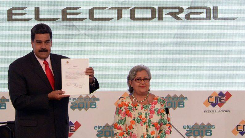 El dictador venezolano Nicolás Maduro (izq.), muestra el documento emitido por el Consejo Nacional Electoral (CNE) que lo proclama Presidente reelecto para el período 2019-2025, junto a la presidente del CNE Tibisay Lucena, en la sede del CNE en Caracas el 22 de mayo de 2018. (FEDERICO PARRA/AFP/Getty Images)