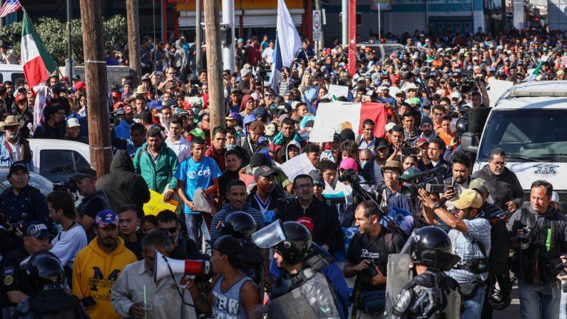 Los migrantes se apresuran frente a la policía antidisturbios al pie de un puente que va desde el campamento de migrantes hasta la entrada peatonal de El Chaparral en el cruce de la frontera de San Ysidro en Tijuana, México, el 25 de noviembre de 2018. (Charlotte Cuthbertson /La Gran Época)