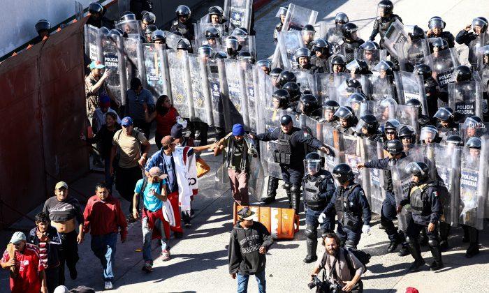 Inmigrantes buscan otra forma de entrar a Estados Unidos, después de que la policía antidisturbios los regresara al oeste del cruce de San Ysidro en Tijuana, México, el 25 de noviembre de 2018. (Charlotte Cuthbertson/La Gran Época)