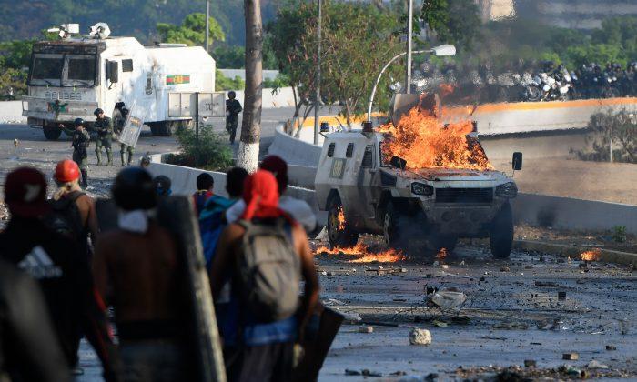 Manifestantes antigubernamentales se enfrentan a las fuerzas de seguridad en Caracas durante la conmemoración del Primero de Mayo, el 1 de mayo de 2019. (Federico Parra/AFP/Getty Images)