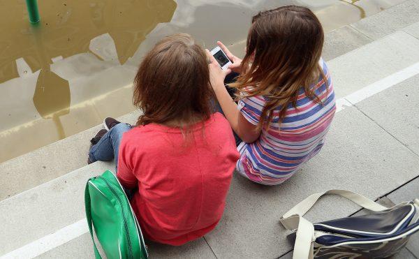 Dos niñas sentadas discuten sobre aplicaciones en sus teléfonos. (Sean Gallup/Getty Images)