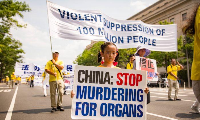 Una niña seguidora de Falun Dafa sostiene un cartel que le pide a China que deje de matar a los presos de conciencia por sus órganos en un desfile en Washington el 20 de julio de 2017. (Benjamin Chasteen/La Gran Época)