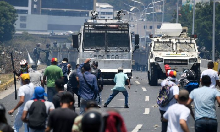 Manifestantes se enfrentan a soldados leales al dictador venezolano Nicolás Maduro después de que las tropas se unieran al presidente encargado Juan Guaidó en su campaña para terminar con la usurpación de Maduro, en las inmediaciones de la base militar La Carlota en Caracas el 30 de abril de 2019. (Federico Parra/AFP/Getty Images)