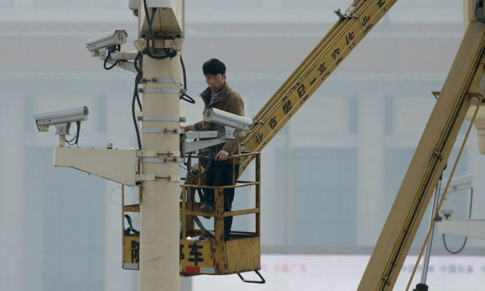 Un técnico revisando las cámaras de seguridad en la Plaza de Tiananmen en Beijing, 31 de octubre de 2013. (Ed Jones/Getty Images/AFP)