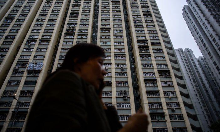 Imagen ilustrativa de un edificio residencial de gran altura en China. Una mujer al teléfono frente a un edificio residencial de gran altura. (Anthony Wallace/AFP/Getty Images)