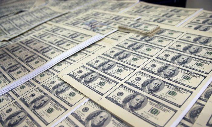 Hojas de billetes de dólar estadounidenses falsificados se exhiben después de que una banda dedicada a la falsificación fue desmantelada en Lima, Perú, el 10 de mayo de 2014. (AFP/Getty Images)