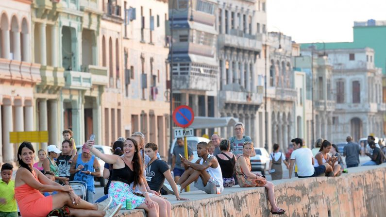 Cubanos y turistas conversan sentados en una zona del malecón, en La Habana (Cuba). EFE/Archivo
