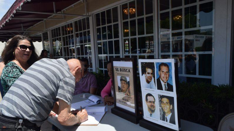Una persona firma un libro con la petición de juzgar a Raúl Castro este jueves, en el exterior del emblemático restaurante Versailles, en Miami, Florida (EE.UU.). EFE